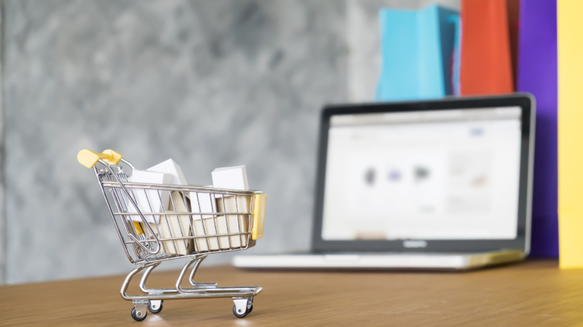 Business theme, internet online shopping concept, shopping delivery, shopping cart carry shopping mail box and blur background of shopping bag and open laptop